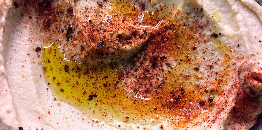 hjemmelaget hummus, hummous med kikerter fra boks og tahini. garnert med olivenolje, røkt paprika.