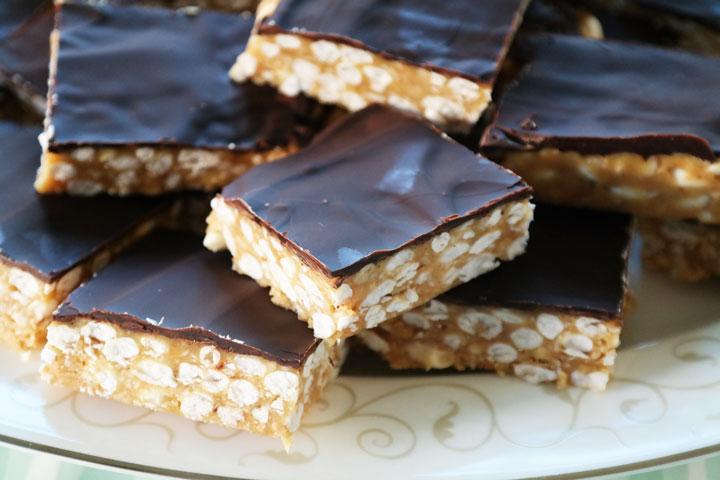 Snickerskake med puffet ris, peanøttsmør og sjokolade. Biter på porselensfat