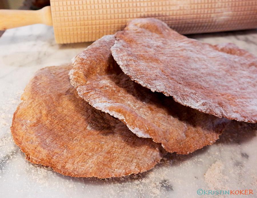 glutenfritt havreknekkebrød med surdeig, ligger på bakebord med kjevle.