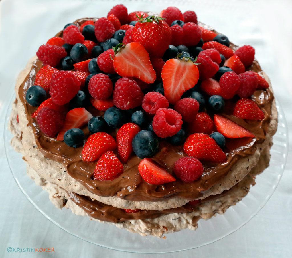 Bountypavlova, pavlova v kokosmarengs med sjokoladebiter, med sjokoladesmørkrem mellom lagene, fylt og pyntet med friske bær.