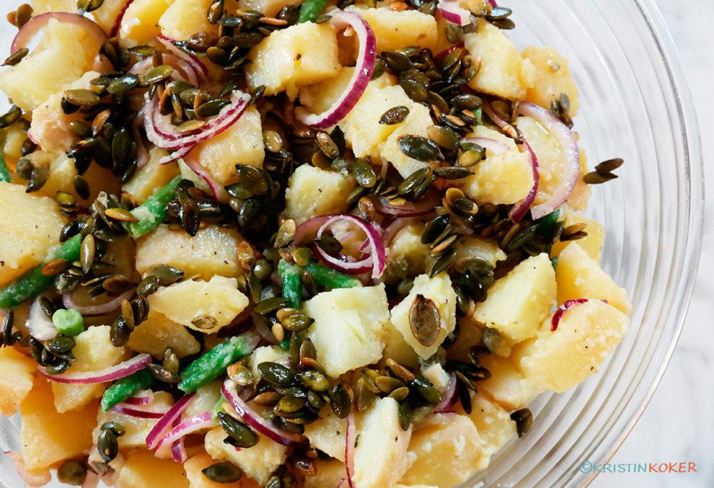Fransk potetsalat med olje-eddikdressing, med hvit balsamicoeddik og ristede gresskarkjerner.
