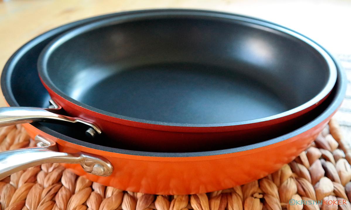 Foto av nye stekepanner, en orange og en lavarød.