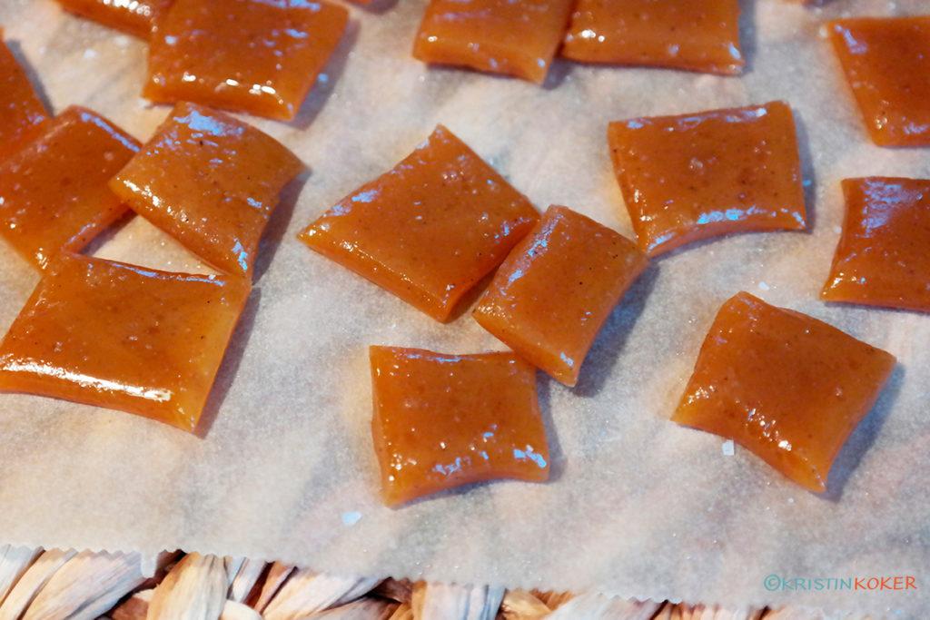 Deilige hjemmelagde karameller med kokosmelk, spredt utover bakepapir, strødd med havsalt.