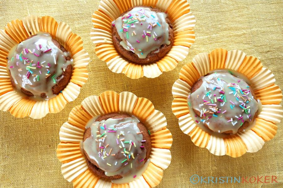 Appelsinmuffins med kokt appelsin, uten melk og gluten. Pyntet med gul melisglasur og strøssel, i gule muffinsformer, påskestemning.