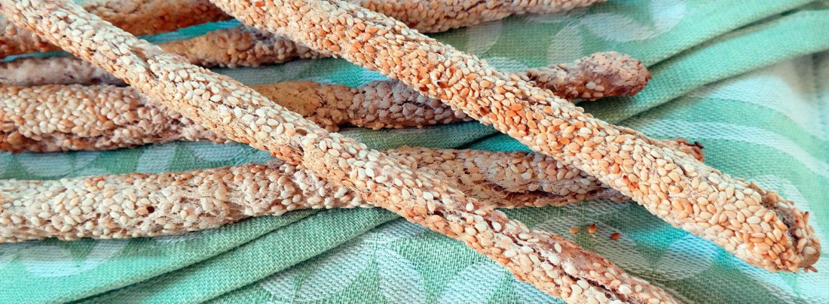 brødpinner med sesamfrø, gluten- og melkefrie, bakt med bakepulverdeig, på mønstrete kjøkkenhåndkle.