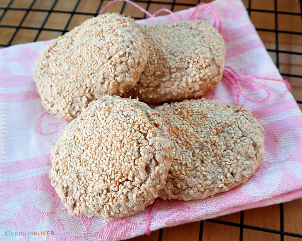 glutenfrie og melkefrie burgerbrød bakt uten gjær, fire burgerbrød på rosa kjøkkenhåndkle.