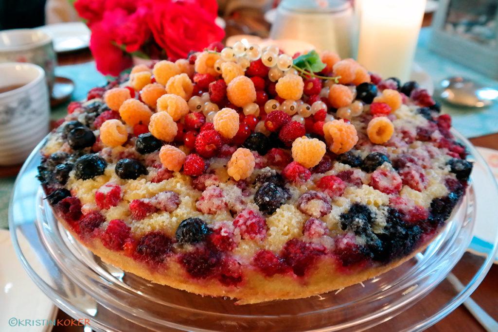 Lys kake med sommerbær og frangipanetopp. Servert på stettefat med blomster og lys i bakgrunnen.